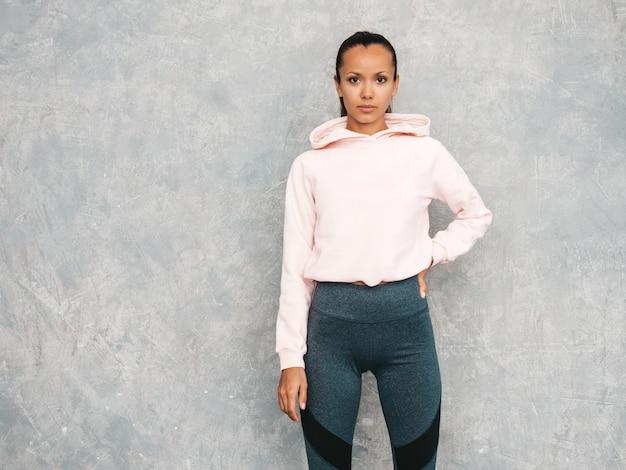 Mooi model met perfect gebruinde lichaam. vrouwelijke poseren in de studio in de buurt van grijze muur