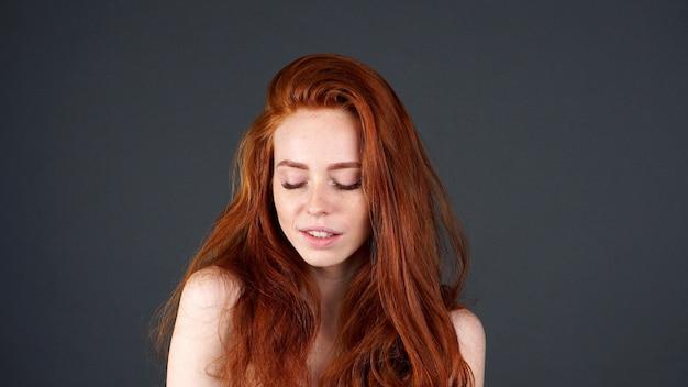 Mooi model met rechte lange rode haren op grijze muur