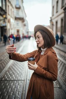 Mooi model neemt selfie terwijl ze haar telefoon in de stad houdt