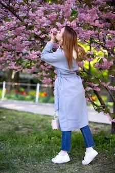 Mooi model poseren in de tuin met sakura. een meisje in een blauwe jas bij een bloeiende japanse kersenboom