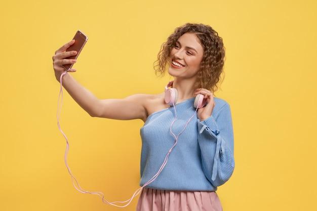 Mooi model poseren met roze koptelefoon en telefoon.