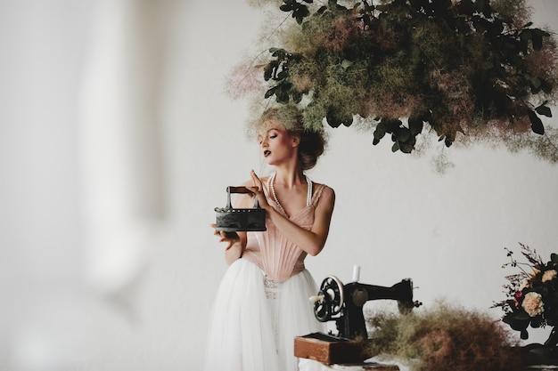 Mooi model staat met een oud ijzer tussen prachtige boeketten in de kamer
