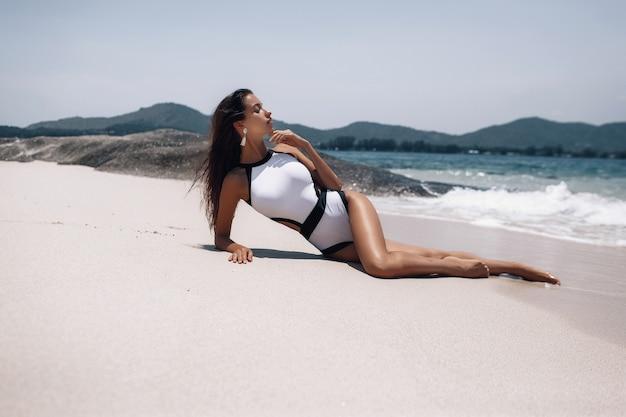 Mooi model vrouw in mode badpak ligt en zonnebaadt op verlaten strand in de buurt van rotsen.