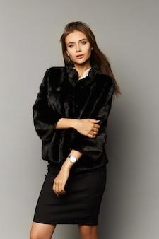 Mooi modelmeisje in rok en bontjas die bij studio wordt geïsoleerd. winterschoonheid met perfecte make-up in luxe outfit geïsoleerd op een grijze achtergrond.