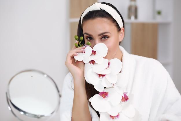Mooi modelmeisje met de verse schone bloemen van de huidholding