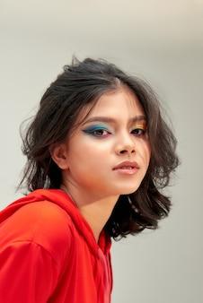 Mooi modelmeisje met helder gekleurde make-up en nagellak