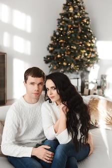 Mooi modelmeisje met lang donker haar en haar knappe vriendje zitten op de bank met een kerstboom op de achtergrond