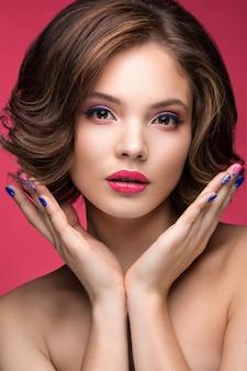 Mooi modelmeisje met lichte make-up en gekleurde nagellak