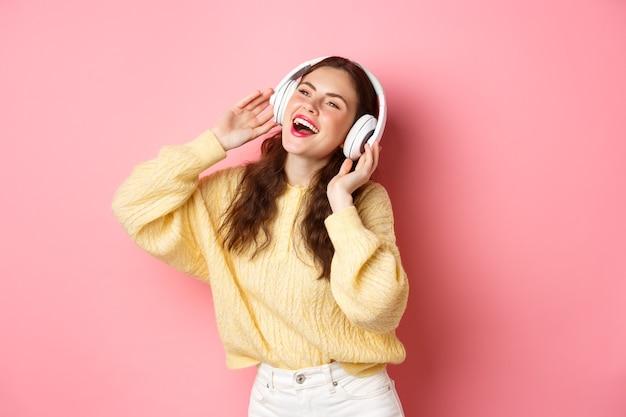 Mooi modern meisje dat favoriete liedje zingt, naar muziek in draadloze hoofdtelefoons luistert, glimlacht en danst, die zich over roze muur bevindt.