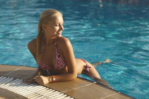Mooi modieus en sexy blond meisje in bikini poseren in zwembad.