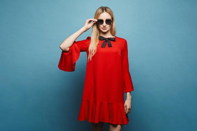 Mooi, modieus en sexy blonde model meisje in stijlvolle zonnebril en in een trendy korte rode jurk met zwarte strik poseren, geïsoleerd