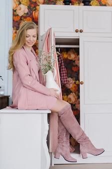 Mooi modieus meisje met lang blond krullend haar in een roze poederachtige jas en laarzen zit op een ladekast in een gezellig interieur. delicate bloem in een vaas in de handen.