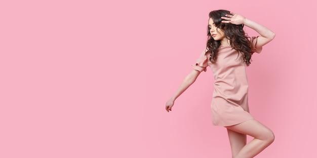 Mooi modieus meisje met lang krullend haar in een roze jurk in de studio op een roze.