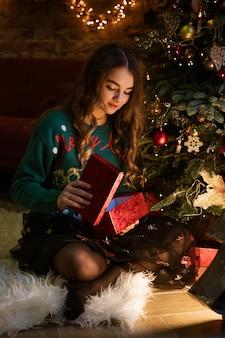 Mooi mooi meisje opent geschenk in groene trui glimlacht en verheugt zich siert de kerstboom met...
