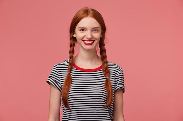 Mooi mooi roodharig meisje met rode lippen, twee vlechten, charmante glimlach, toont witte gezonde tanden, gekleed in gestripte t-shirt, geïsoleerd