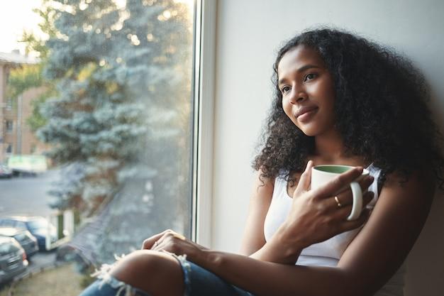 Mooi mulat donkerhuidig meisje in stijlvolle kleding die thuis bij het raam ontspannen, grote mok vasthouden, genieten van verse koffie of thee, dromerige gezichtsuitdrukking hebben, aan iets plezierigs denken