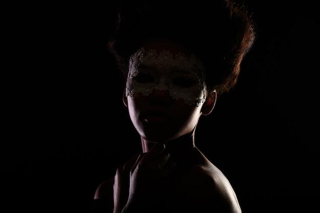 Mooi mysterieus amerikaans zwart vrouwelijk meisje in een venetiaans masker dat op zwarte wordt geïsoleerd