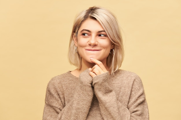 Mooi mysterieus europees meisje in stijlvolle, knusse trui die raadselachtige gezichtsuitdrukking heeft verbaasd, wegkijkend en glimlachend, met een idee op de proppen kwam, nadenkend over plan geïsoleerd op blinde muur