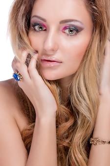 Mooi naakt blond meisje met lichte make-up en lang gekruld haar op witte achtergrond. mode-opname.