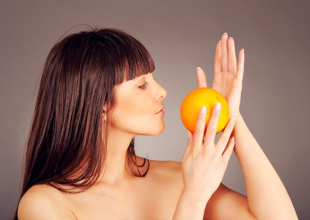 Mooi naakt meisje met een sinaasappel