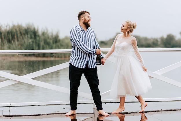Mooi net getrouwd dansen op blote voeten en plezier hebben op de pier aan het water.