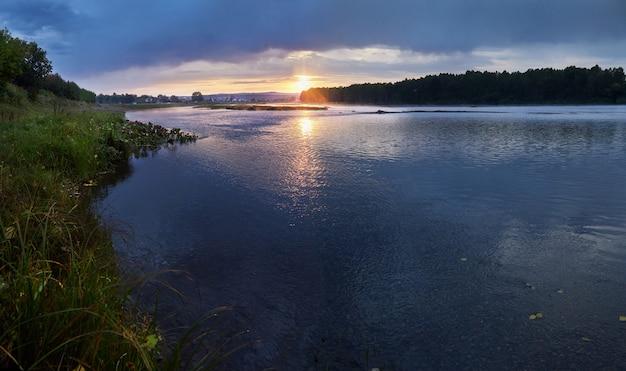 Mooi ochtendlandschap van de rivier in het dorp, zonsopgang op het platteland. de blauwe lucht wordt weerspiegeld in de rivier