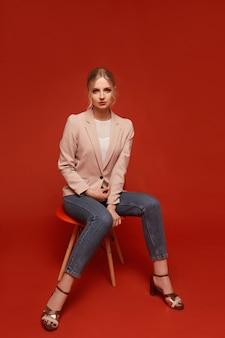 Mooi ogend aantrekkelijk glamoureus modelmeisje dat een beige blazer en jeans draagt die op de stoel zit, die over rode achtergrond wordt geïsoleerd