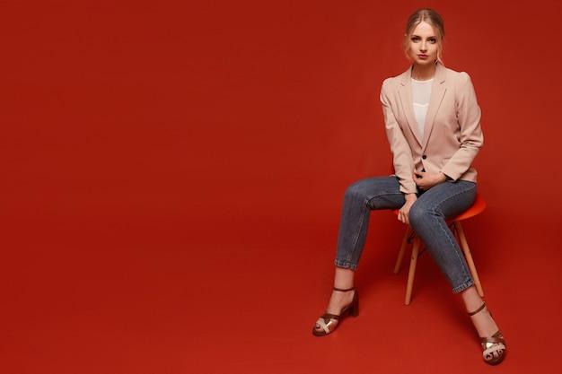 Mooi ogende aantrekkelijke jonge modelvrouw die een beige blazer en een spijkerbroek draagt die op de stoel zit, die over rode achtergrond wordt geïsoleerd