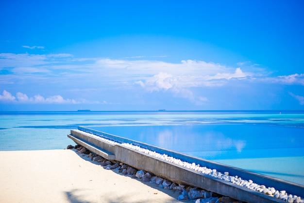 Mooi oneindig zwembad in luxetoevlucht bij tropisch land