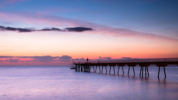 Mooi ontwaken van lucht met weinig wolken en zee naast een loopbrug