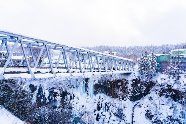 Mooi openluchtaardlandschap met shirahige waterval en brug in sneeuw wintertijd