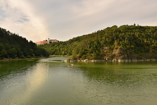 Mooi oud kasteel bitov in het bos boven de dam. vranov dam. zuid-moravië - tsjechische republiek