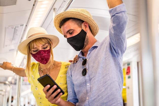 Mooi paar dat beschermende gezichtsmaskers draagt en kust tijdens covid-19 pandemie