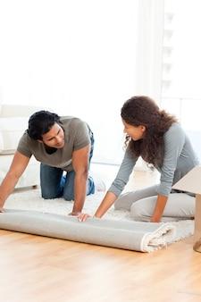 Mooi paar dat een tapijt samen in de woonkamer rolt