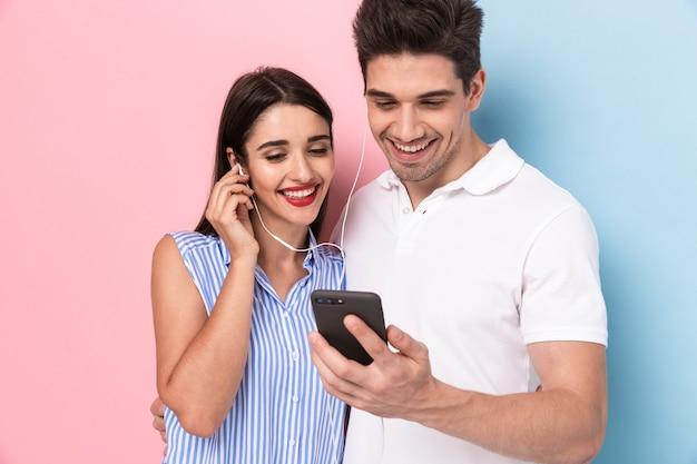 Mooi paar dat oortelefoons samen draagt en smartphone gebruikt, die over kleurrijke muur wordt geïsoleerd