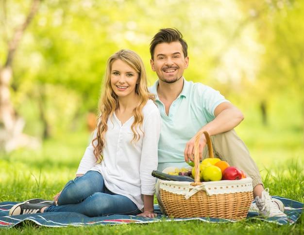 Mooi paar dat picknick op het gazon in de zomerpark heeft.