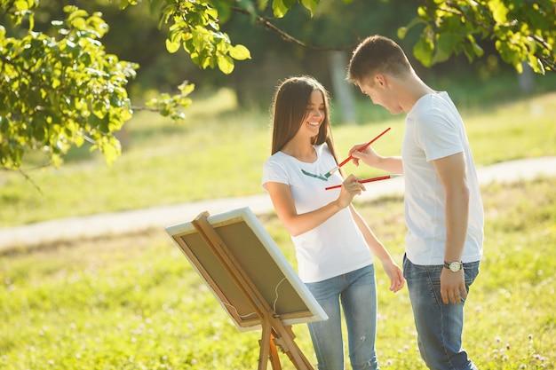 Mooi paar dat pret heeft bij openlucht in openlucht. jonge man en vrouwentekening door kleurrijke verven op elkaar `s t-shirts met borstels dichtbij de schildersezel op de aard.