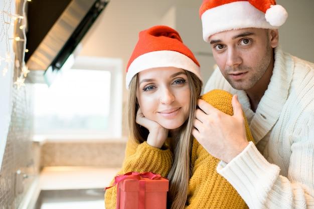 Mooi paar die in kerstmanhoeden camera bekijken
