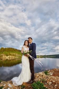Mooi paar die in liefde terwijl status op grond door meer kussen. bruidspaar bij zonsondergang, blauwe wolkenhemel, liefde en tedere gevoelens. verliefde paar rusten. huwelijksceremonie buitenshuis. perfect stel
