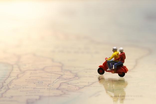 Mooi paar die rode cijfermotorfiets of autoped berijden op uitstekende wereldkaart