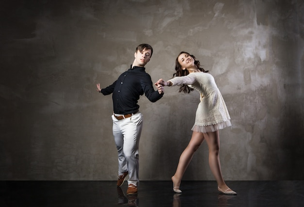 Mooi paar in de actieve ballroomdans op donkere achtergrond