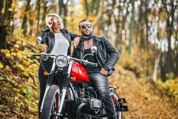 Mooi paar in de buurt van rode motorfiets op de weg in het bos