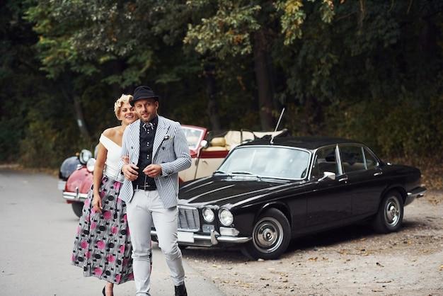 Mooi paar in ouderwetse slijtage in de buurt van retro auto met bos op de achtergrond.