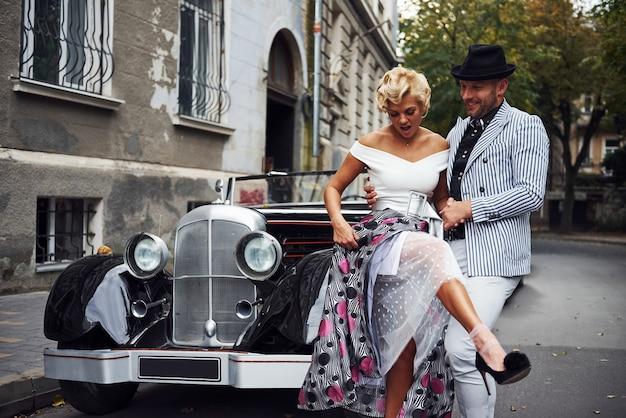 Mooi paar in ouderwetse slijtage is in de stad met retro auto.