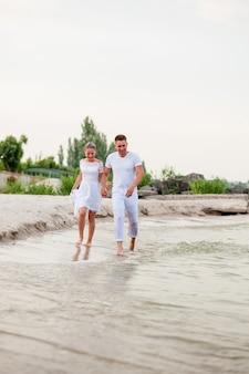 Mooi paar in witte kleren lopen op de zee