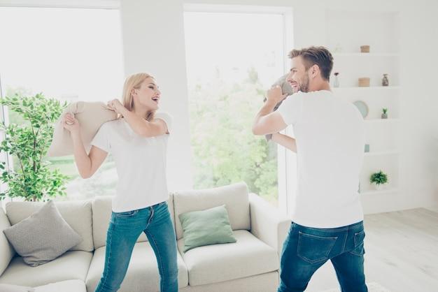 Mooi paar in witte t-shirts en spijkerbroek vechten met kussens licht interieur