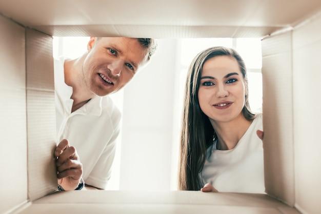 Mooi paar kijkt in een grote kartonnen doos Premium Foto