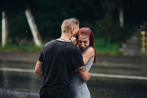 Mooi paar knuffelen buiten in de regen