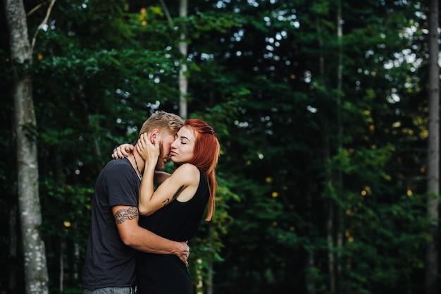 Mooi paar knuffelen elkaar op de achtergrond van het bos
