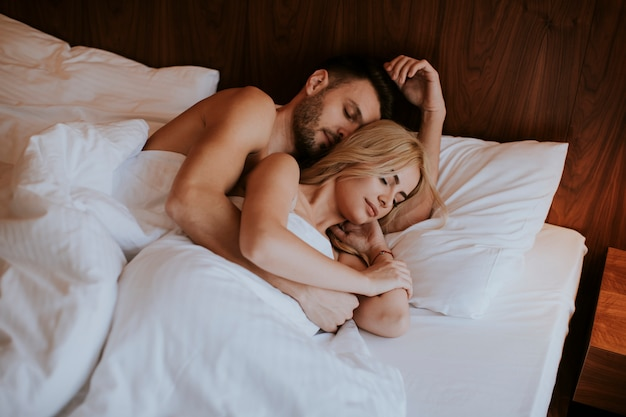 Mooi paar knuffelen op hun bed thuis